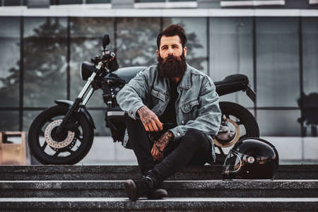 Brutal pensive man in denim jacket is sitting on the stairs close to his motorbike neaar glass building. Reklamní fotografie