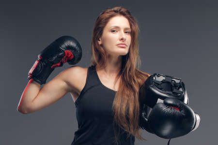 Beautiful woman wearing boxer gloves is holding protective helmet while posing for photographer.