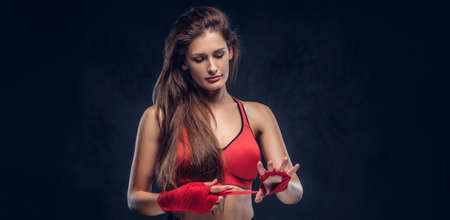 Beautiful cheerful woman in red bra is wearing her gloves before boxing. Reklamní fotografie