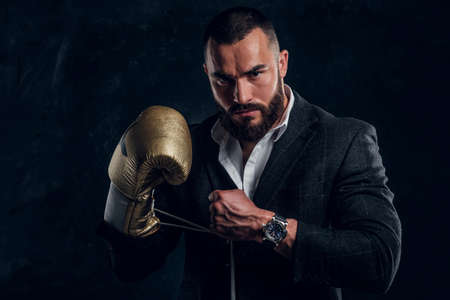 Serious brutal man in suit and golden boxing glove is posing for photographer at dark photo studio. Reklamní fotografie
