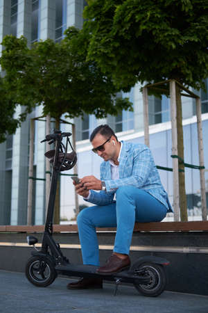 Styilish modern man with electro scooter is sitting on the bench while chatting on his mobile phone. Reklamní fotografie