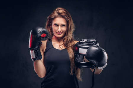 Happy smiling woman wearing boxer gloves is holding protective helmet at studio.