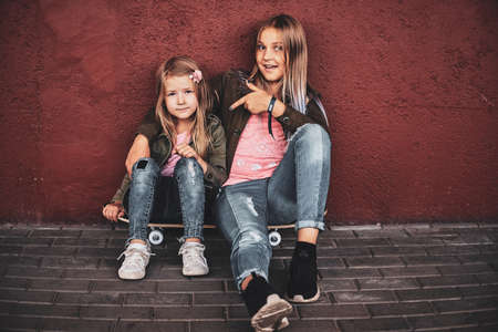 Two pretty little girls are chilling on the street while sitting on the skateboard. Reklamní fotografie