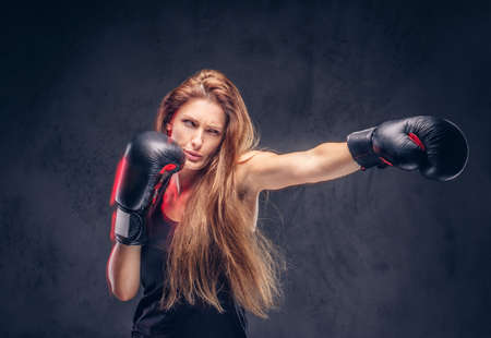 Beautiful woman with long hair is demonstraiting her hit at studio. She is wearing boxing gloves. Reklamní fotografie