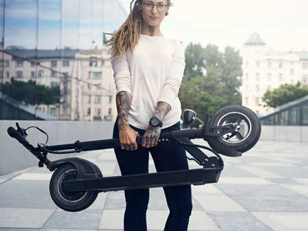 Young tattooed woman with dreadlocks is posing for photographer while holding folded electro scooter. Stockfoto