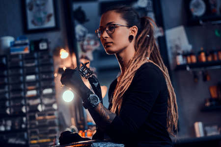 Pretty expirienced tattoo artist in glasses is tuning her new tattoo machine before tattooing session. Reklamní fotografie