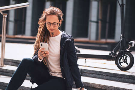 Beautiful pensive woman with tattooes, dreadlocks and electro scooter is chatting by mobile phone while sitting on the stairs. Stock Photo