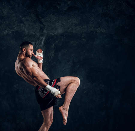 Muscular handsome fighter with torso is demonstraiting his power at dark photo studio.