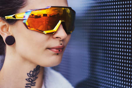 Portrrait of girl in big toned glasses and with piercing over interesting wall with dots.