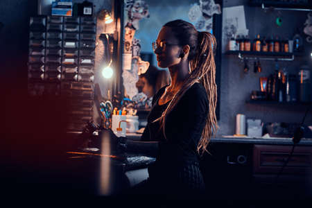 Portrait of young woman with dreadloks and glasses which is sitting at her tattoo studio. Reklamní fotografie