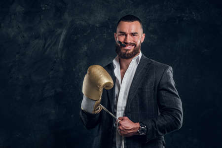 Cheeky bearded man in suit and golden boxing glove is smiling with mouth guard in his mounth. Stock fotó