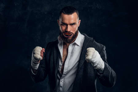 Angry bearded businessman in suit and protective kickboxing gloves is posing for photographer at dark photo studio.