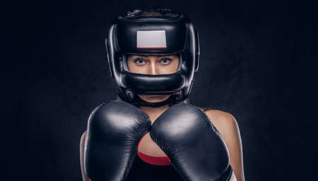 Brave woman is ready to fight, she is wearing boxer gloves and protective helmet. Stock Photo
