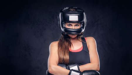 Brave cheeky woman is standing crosses her hands, she is wearing boxing gloves and helmet. Stock Photo