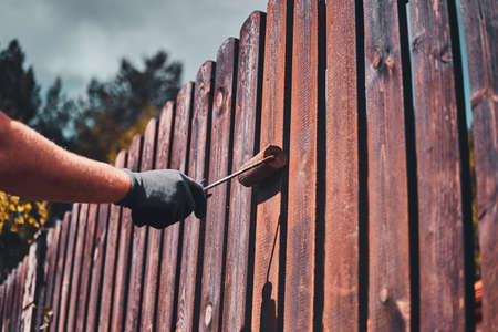 Process of fence renovation at bright sunny day by man in protective gloves.