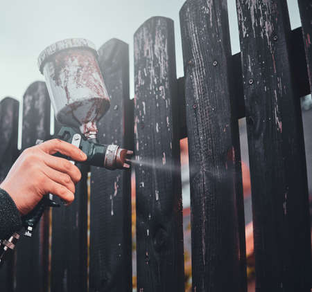Man is applying paint to the old fence using airbrush at his garden.