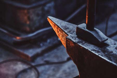 Close up photo shoot of hammer and anvil at dark smith workshop.