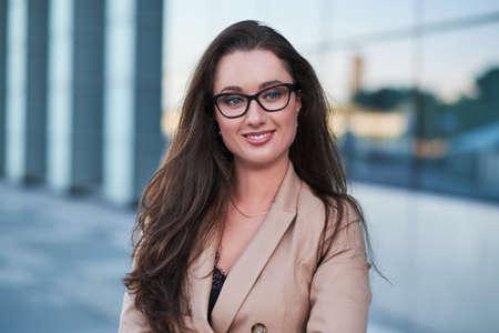 Porträt einer erfolgreichen Geschäftsfrau mit einem charmanten Lächeln, die auf der Straße mit interessanter Architektur im Hintergrund posiert. Standard-Bild