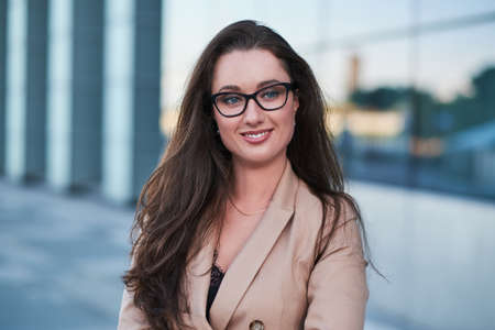 Portrait of a successful businesswoman with a charming smile posing on the street with interesting architecture at the background. Imagens