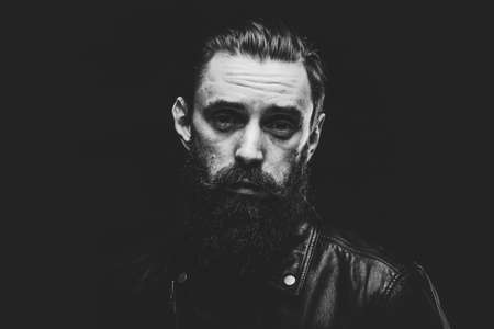 Black and white photo of sad man with beard on the dark background.