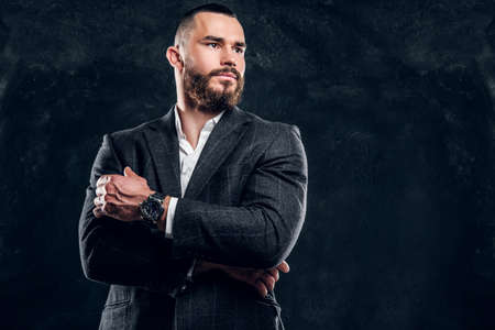 Handsome successful businessman is posing for photographer on the dark background.
