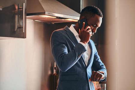 Jeune homme africain en chemise blanche discute par téléphone portable dans la cuisine. Banque d'images