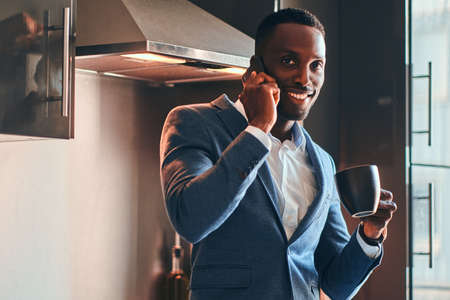 Elegant african man is enjoying his morning coffee while talking by mobile phone at his kitchen. Stock Photo