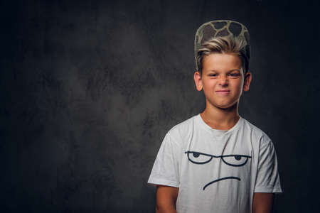 Young cheeky hooligan in cap is posing for photographer at photo studio on the dark background. Reklamní fotografie