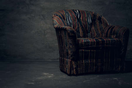 Old armchair in an empty dark studio
