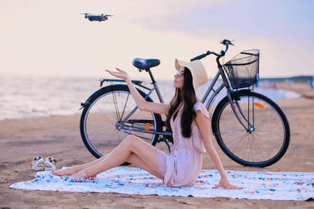 Pretty happy woman is trying to catch a drone while chilling on the beach next to her bike.
