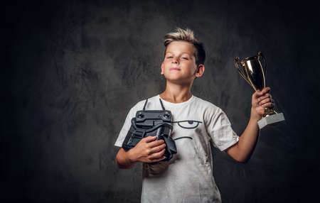 Young happy boy won the competition in virtual reality games and got the cup. Standard-Bild