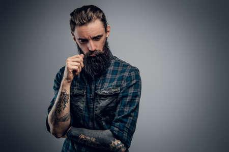 El hombre barbudo y flaco con tatuajes siente desesperación y tristeza mientras piensa en la vida.