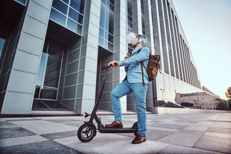 Pensive man in protective helmet and sunglasses is smoking vape while holding his electrical scooter.