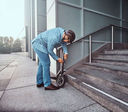 Modern trendy man is locking his electrical scooter near his job at street. 스톡 콘텐츠 - 129364868