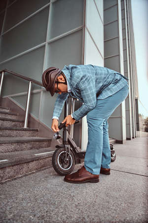 Modern trendy man is locking his electrical scooter near his job at street. 스톡 콘텐츠