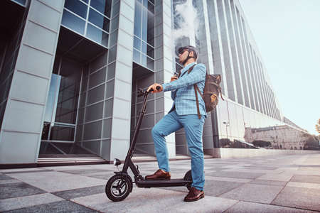 Pensive man in protective helmet and sunglasses is smoking vape while holding his electrical scooter. 스톡 콘텐츠 - 129364955