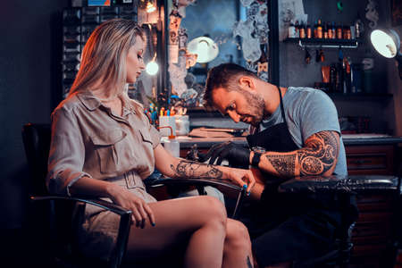 Dilligent focused tattoo artist is creating new tattoo on young womans hand at tatoo studio.