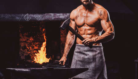 Powerful bearded blacksmith with torso and protective apron is standing near working stove with hammer in his hand.
