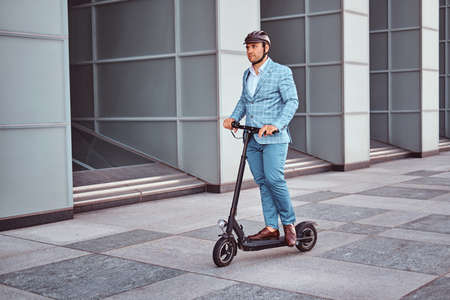 Miggle aged broker in protective helmet is driving his new electro scooter to the work.