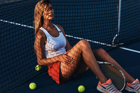 Pensive girl is relaxing near tennis net on the floor while posing for photographer.