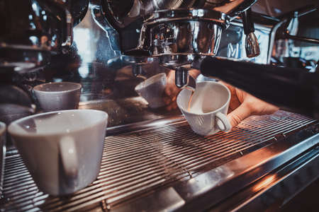 Process of coffee making using coffee machine at restaurant by talanted barista.