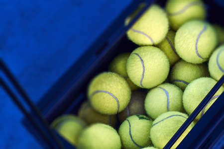 Box full of tennis balls is standing on the floor at tennis court.