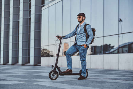 Cheerful modern man is driving his electro scooter near his office after long hard day. 스톡 콘텐츠 - 129400173