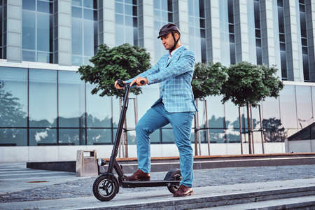 Miggle aged broker in protective helmet is driving his new electro scooter to the work. 스톡 콘텐츠 - 129400163
