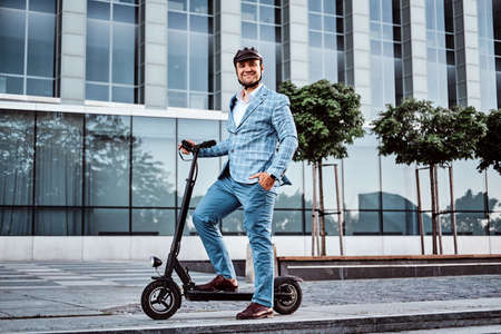 Miggle aged broker in protective helmet is driving his new electro scooter to the work. 스톡 콘텐츠 - 129400165