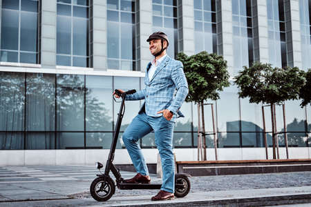 Miggle aged broker in protective helmet is driving his new electro scooter to the work. 스톡 콘텐츠 - 129400162