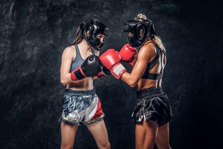 Processo di lotta tra due pugili femminili in guanti e caschi su sfondo scuro.
