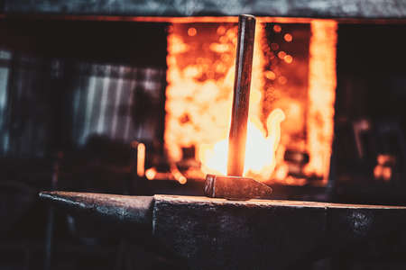 Hammer on anvil at dark blacksmith workshop with fire in stove at background. 스톡 콘텐츠 - 129400472