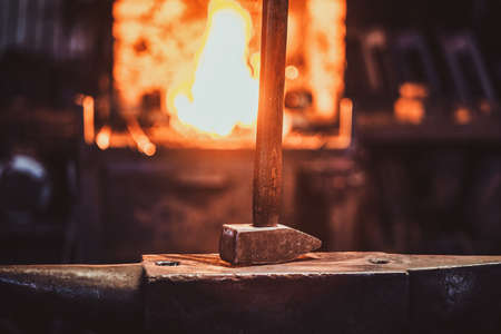 Hammer on anvil at dark blacksmith workshop with fire in stove at background.