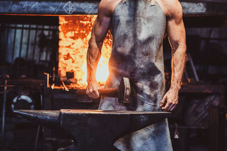 Muscular blacksmith in protective apron at his workshop with hammer in his hands. There are fire at background. 스톡 콘텐츠 - 129400561